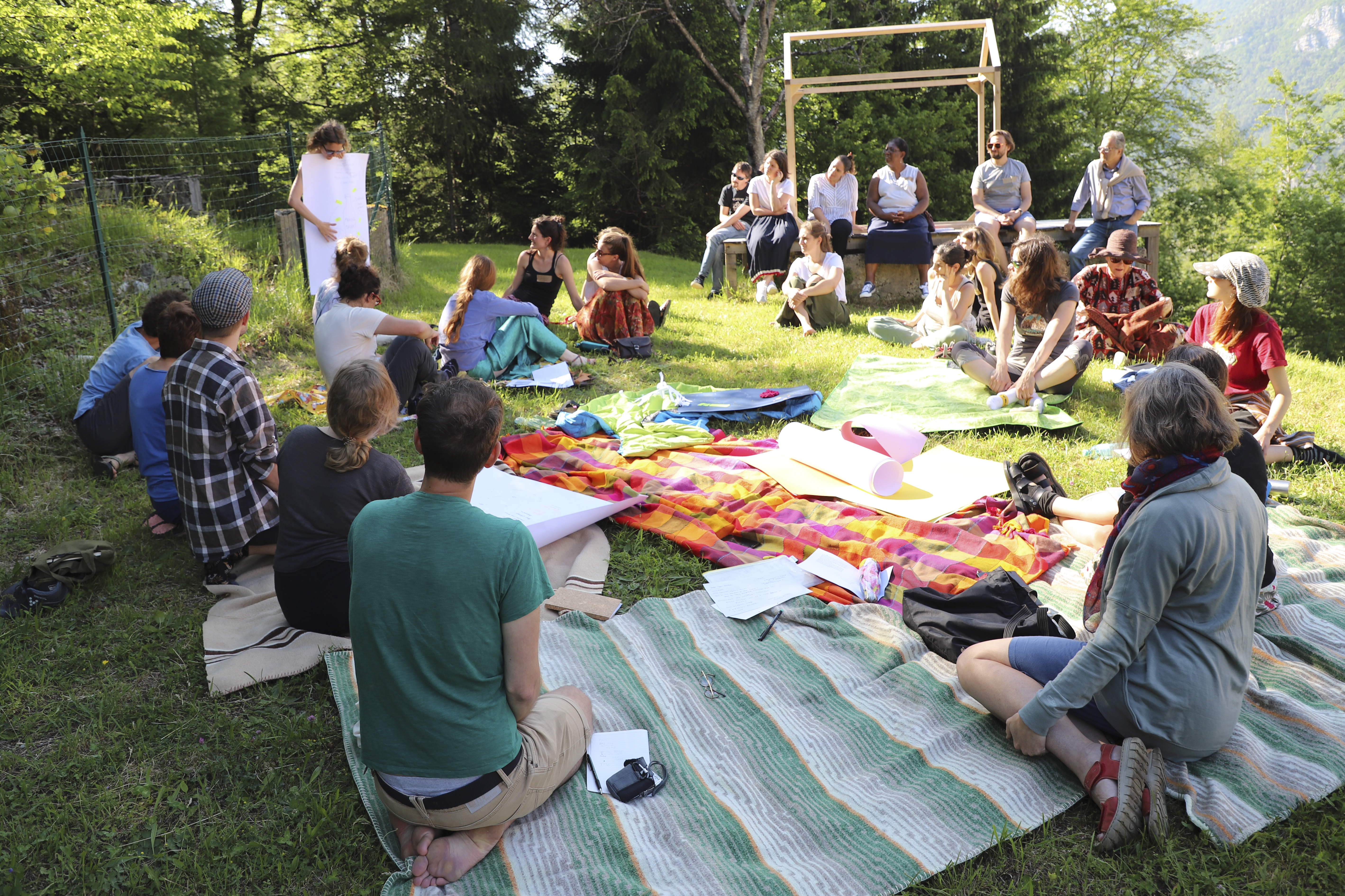 community economies practice exchange - community economies practitioners sitting in a circle on the grass sharing their workshop outcomes